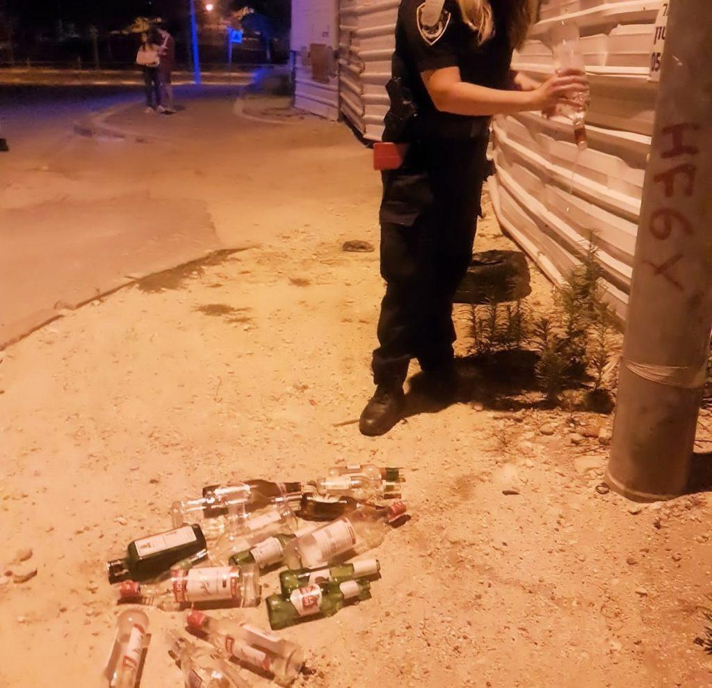 שוטרים שופכים בקבוקי אלכוהול (צילום: דוברות המשטרה)