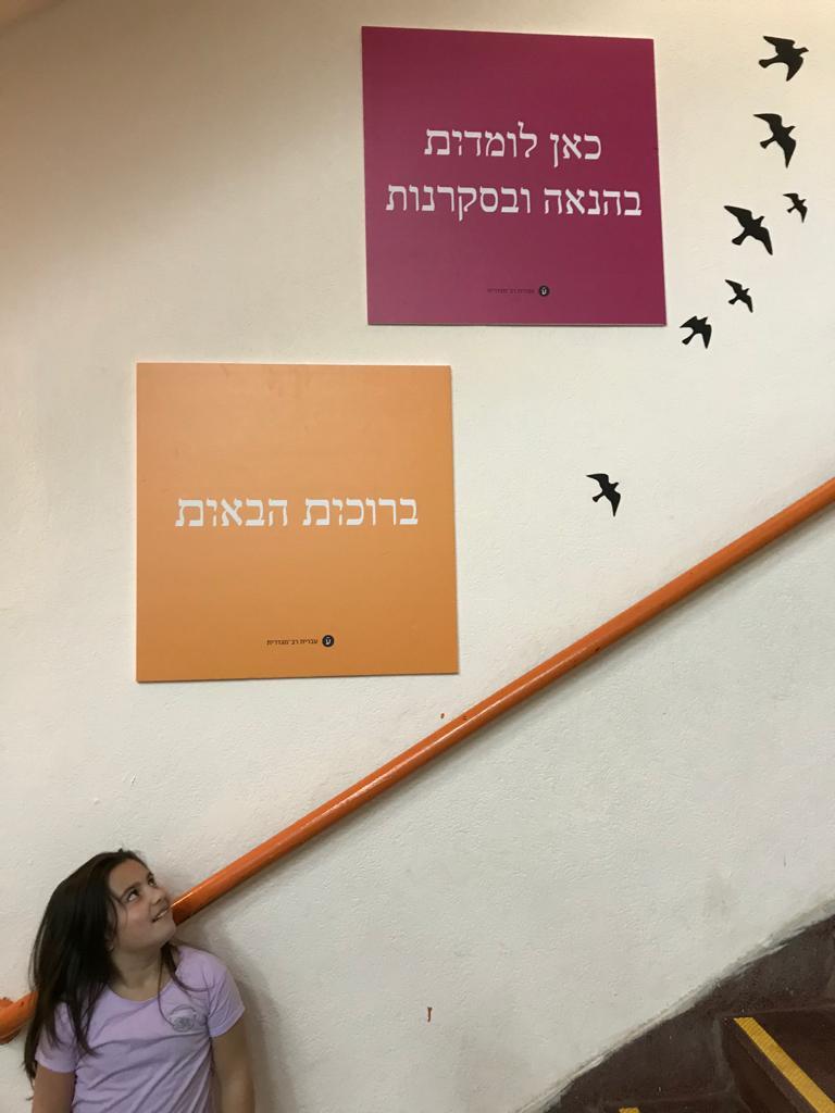 אביגיל אלקובי עם השלטים הרב מגדריים (צילום: יניב אלקובי)